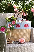 Raffia shopping bag decorated with knitted trim and knitted roses on pale rattan armchair next to climbing rose