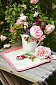 Romantic vase of garden flowers on knitted cloth with rose motif