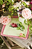 Romantic china vase of garden flowers on knitted cloth with rose motif