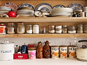 Stacks of various plates, storage jars and ceramic pots on kitchen shelves