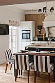 weiße Landhausküche mit Kücheninsel, gedecktem Esstisch mit braun gestreiften Polsterstühlen
