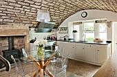 Elegante Landhausküche mit rustikaler Gewölbedecke, Designermöbeln und traditionellem Kaminofen