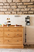 Black vintage payphone on white brick wall next to solid oak chest of drawers below vaulted stone ceiling