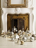 Traditional Christmas decorations in silver and gold in front of fireplace with brass doors