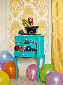 Christmas decorations on top of and in drawers of turquoise console table amongst balloons on floor