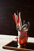 Chopsticks and cutlery in vintage beakers in pot with Oriental pattern