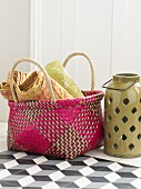 Colourful wicker basket next to ceramic candle lantern