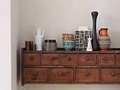 Collection of retro dishes and vases on top of rustic wooden cabinet with small drawers mounted on wall