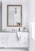 White vanity with marble top and wall mirror on tiled wall