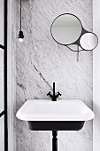 Washbasin with black fittings in front of marble wall with round mirrors