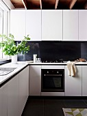 White corner kitchen with black splash guard and green oak leaf branches in front of window
