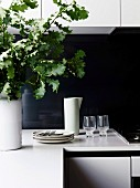 Dishes in front of black splash protection and oak leaves in vase in white kitchen