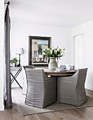 Round table with gray leather armchairs in the dining room