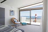 Airy bedroom with window front and sea view, woman on glass balustrade on terrace