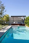 Pool with glass partition to the garden area and covered loungers