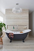 Freestanding vintage bathtub with stand mixer in designer bathroom with natural stone cladding