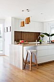 White designer kitchen with island made of natural stone