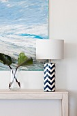 Elegant, blue and white table lamp next to a glass vase in front of a maritime painting