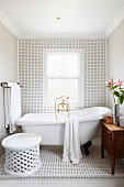 Black and white tiles and free-standing bathtub in simple bathroom