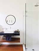 Glazed shower cubicle, round mirror and floating washstand with black top