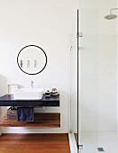 Verglaste Duschkabine neben rundem Wandspiegel und Waschbecken auf Waschtischplatte
