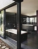 Bathtub, glossy black wall tiles and open sliding terrace doors in bathroom