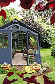 Anthracite greenhouse with sliding door in the garden