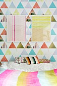 Two frame graphic artworks on colourful wallpaper above scatter cushions on bed
