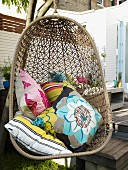 Floral and striped cushions in wicker hanging chair on terrace