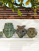 Painted ethnic clay masks on shelf on screen