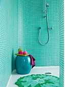 Turquoise mosaic wall tiles and toiletries on drum-shaped stool in shower area