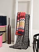 Blankets hung over white-painted ladder used as shelves next to dark floor vase