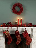 Mantelpiece festively decorated with Christmas stockings, lit candles and red decorations