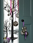 Christmas baubles hung from door knob, half-open double doors with view of stylised tree decorated with silver baubles and gifts on floor