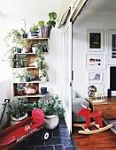 Plants on wooden shelves on balcony next to open sliding door
