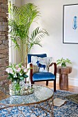 Blue armchair, palm tree and glass table in corner of room