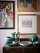 Turquoise ceramics on vintage wooden trunk and ethnic pictures on pastel pink wall