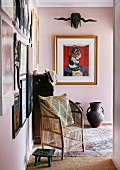Wicker armchair, footstool and gallery of pictures on pink walls in foyer
