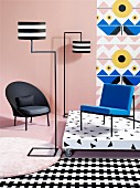 Black armchair, designer standard lamp, blue chair on platform against wallpaper and mixture of patterns