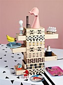 Miniature accessories on wooden chest of drawers printed with mixture of patterns