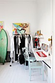 Colourful comic-style artwork above clothing rail holding black and white clothing in hipster-style period apartment
