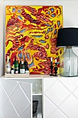 Colourful picture, bottles of spirits and table lamp on top of white sideboard