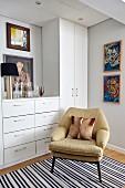 Gemütlicher Retro Sessel vor weißem Einbauschrank und modernen Portraitgemälden