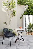 Black wire chair and round garden table on terrace