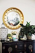 Round gold frame mirror above ethnic piece of furniture with lantern, green plant and stack of porcelain plates