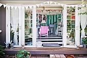 Blick in eklektischen Wohnbereich mit rosafarbenem Korbsessel, auf Wimpelketten und geöffnete Fenstertüren