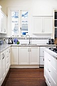 White corner country kitchen with black and white border under wall cupboards