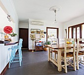 Country-style dining area, light blue bar stools on kitchen counter with red wall clock