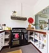 Kitchen with hatch, black gas stove and red wall clock
