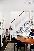 Couple with dog in dining room with bookcase under stairs